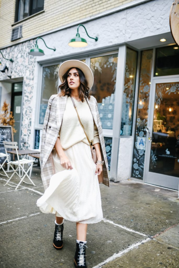 Lulus NYFW outfit with midi skirt, cream sweater and plaid jacket